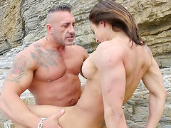 Body builder and a fit girl have athletic sex on the beach