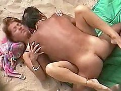 Guy drills his wife's pussy in missionary position on a beach
