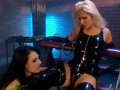 Two hot latex wearing lesbos ride dildos and eat pussy in dungeon