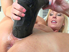 Intriguing blonde chick and her session with the large black toy