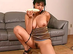 Asian in a slutty gold dress and heels fucks her food